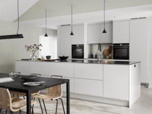 Lys grått kjøkken med benkeplate av rustfritt stål