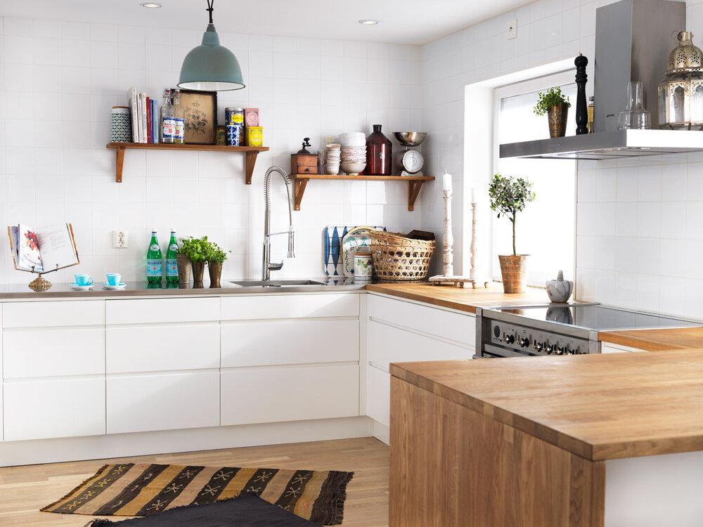 Hvit kjøkkeninnredning med benkeplate av tre