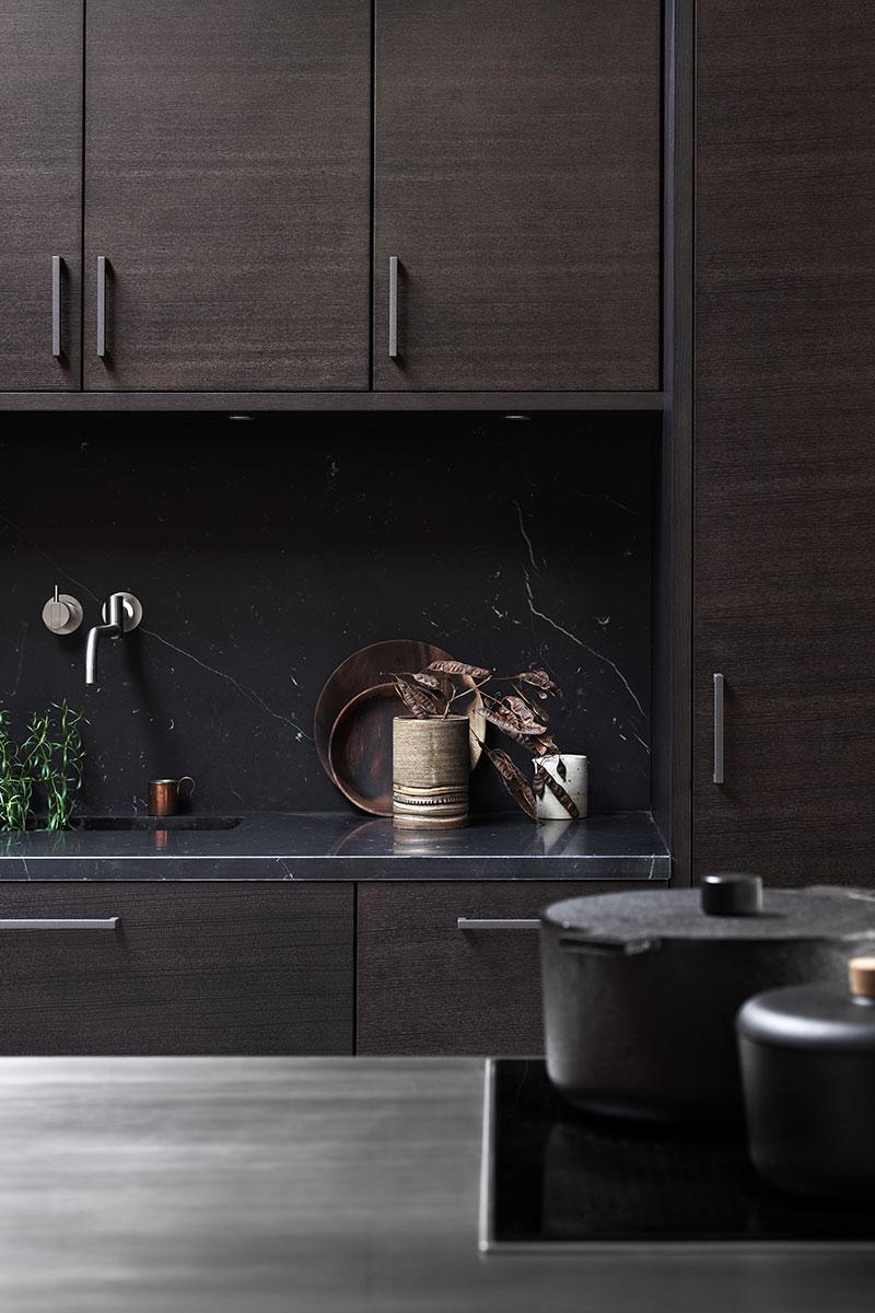 Beiset kjøkken i tre med benkeplate av rustfritt stål og med svart marmor